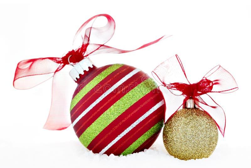与丝带雪的圣诞节红色绿金球装饰品 免版税库存照片
