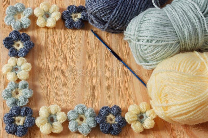 与丝球的手工制造五颜六色的钩针编织花在木桌上 库存图片