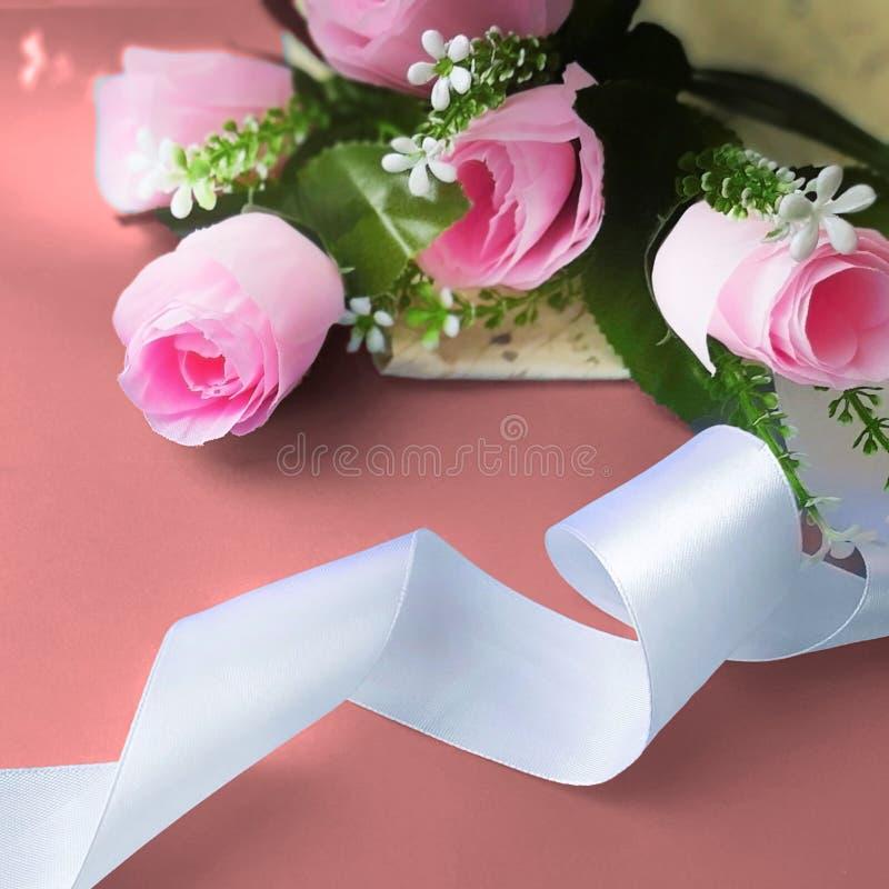 与丝绸丝带的桃红色玫瑰在珊瑚背景 免版税库存照片