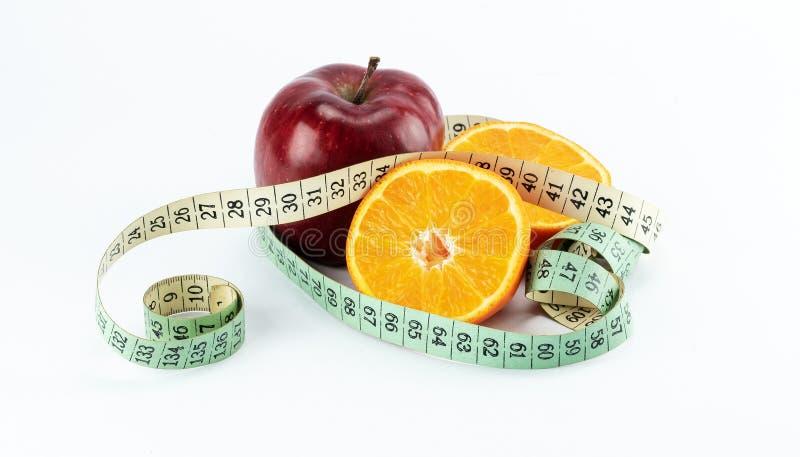 与两个一半的红色苹果桔子包裹与测量的磁带 免版税库存图片