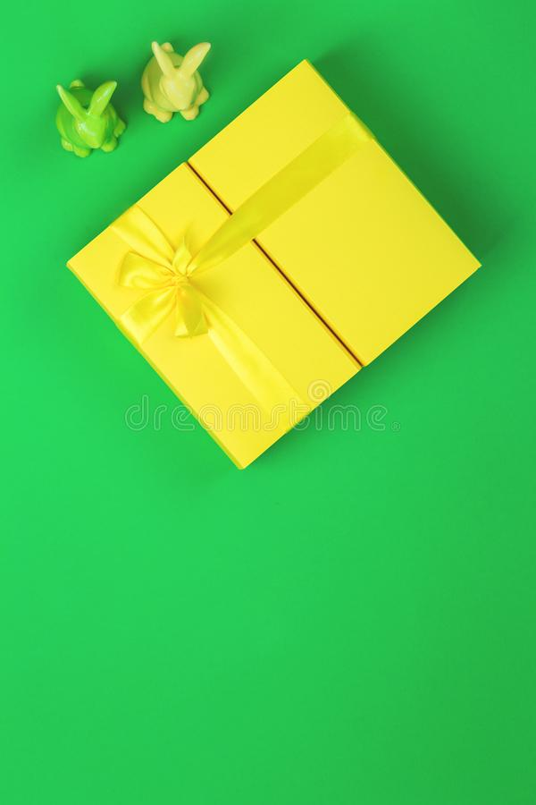 与两个兔宝宝的黄色复活节giftbox在绿色背景 免版税图库摄影