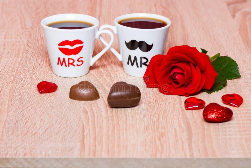 与两个咖啡杯和玫瑰色花的情人节背景 库存图片