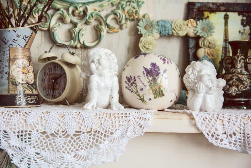 与两个天使、时钟和被编织的布料的葡萄酒桌 免版税库存图片