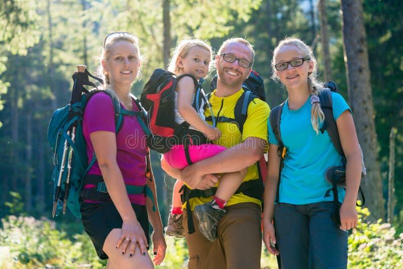 与两个女儿的家庭远足的在森林 免版税库存照片