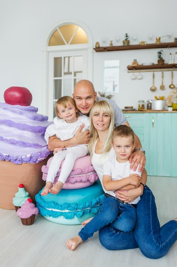 与两个孩子和大冰淇凌的愉快的家庭 3个照相机长沙发系列女孩查找关于坐的母亲橙色纵向他们那里 免版税库存图片