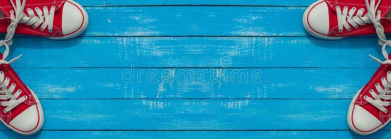 与两个对的横幅蓝色木表面上的红色青年鞋子 免版税库存图片