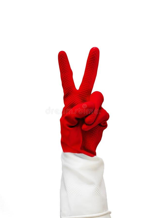 与两个手指折叠在红色橡胶手套的手,显示什么标志一切是凉快的 在白色背景的孤立 库存照片