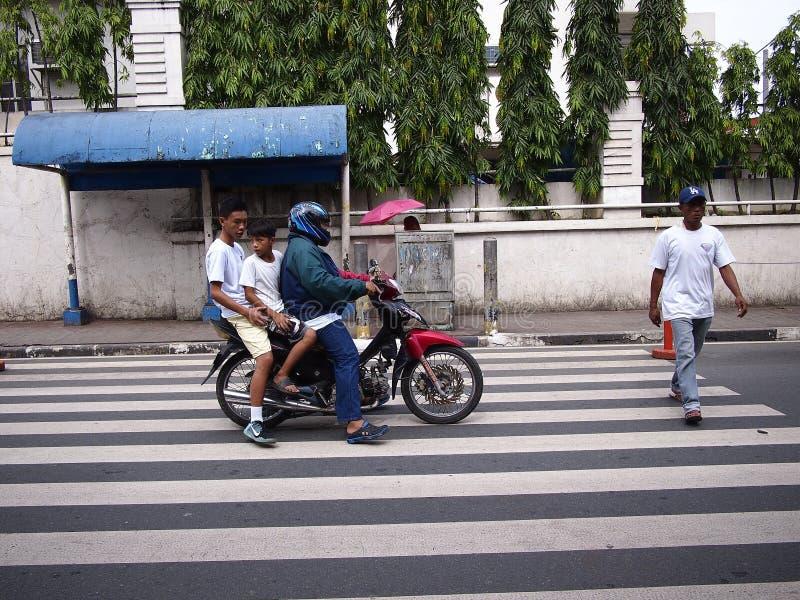 与两位乘客的一个摩托车车手停下来让一个人通过在一条步行车道 免版税库存图片