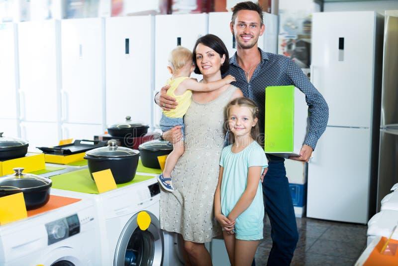与两儿童购物的笑的家庭 库存图片