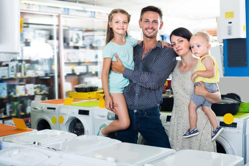 与两儿童购物的年轻家庭 库存图片