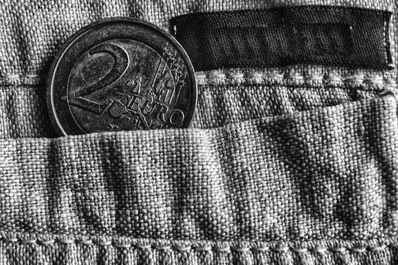 与两在亚麻布裤子的口袋的欧元的衡量单位的欧洲硬币有黑条纹的,单色射击 库存图片