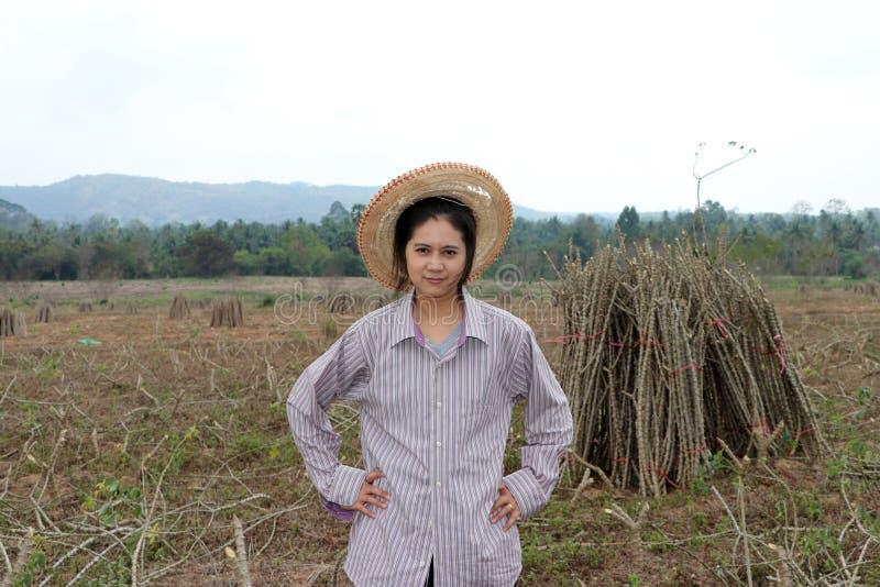 与两手插腰的女性农夫身分和在农场一起切开堆珍珠粉植物的肢体  库存照片