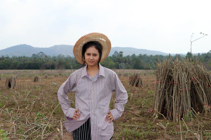 与两手插腰的女性农夫身分和在农场一起切开堆珍珠粉植物的肢体  免版税库存照片