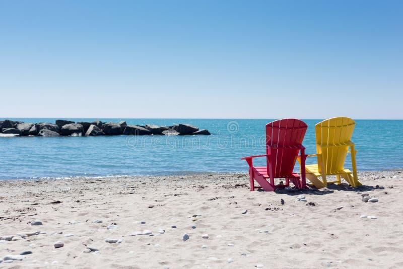 与两把五颜六色的adirondack椅子的海滩场面 图库摄影