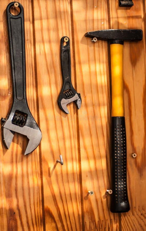 与两把钢扳手和垂悬在木墙壁上的锤子的明亮的背景 库存照片