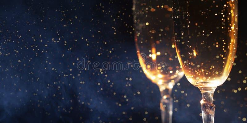 与两杯的圣诞节装饰香槟和光在木背景,新年快乐 免版税库存照片