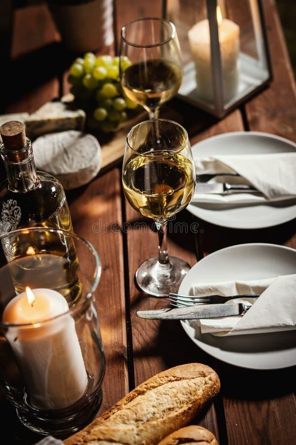 与两杯的浪漫晚餐酒和快餐在一张老木桌上 库存照片