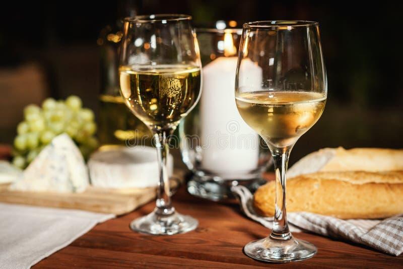 与两杯的浪漫晚餐酒和快餐在一张老木桌上 库存图片