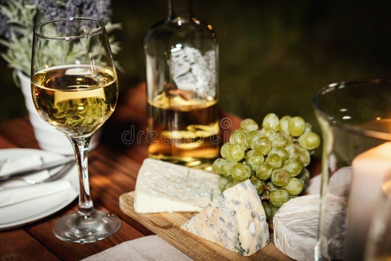与两杯的浪漫晚餐酒和快餐在一张老木桌上 免版税库存照片