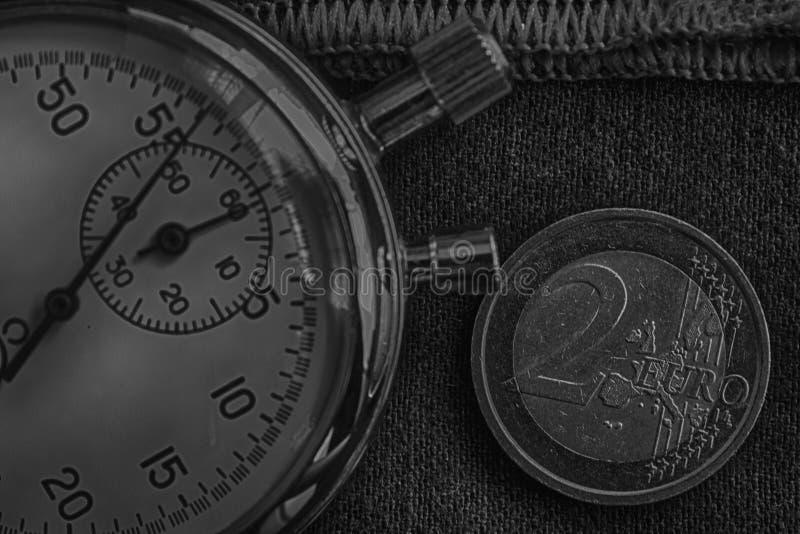 与两欧洲和秒表的衡量单位的欧洲硬币在破旧的牛仔布的与红色条纹背景-企业背景 免版税库存图片