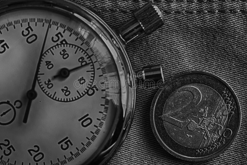 与两欧洲和秒表的衡量单位的欧洲硬币在破旧的牛仔布背景-企业背景的 库存图片
