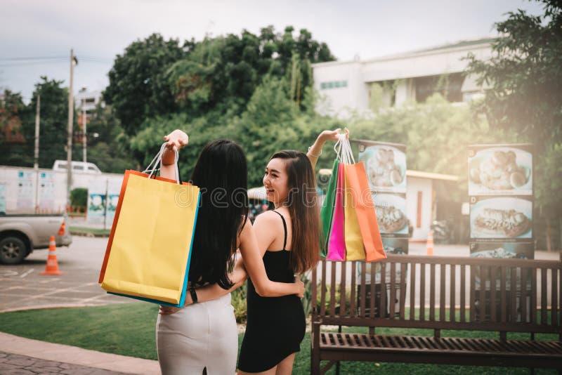 与两美丽的亚洲妇女藏品购物带来的背面图在室外购物的市场上 免版税库存图片