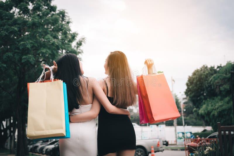 与两美丽的亚洲妇女藏品购物带来的背面图在室外购物的市场上 库存图片