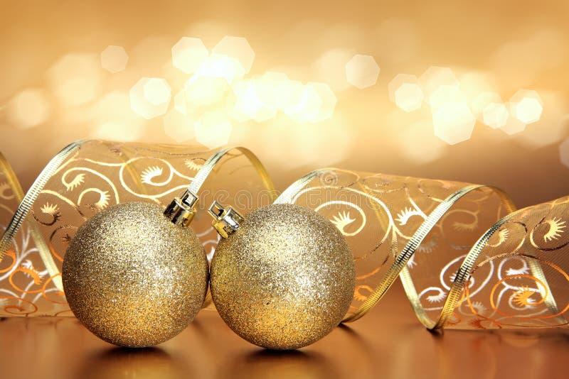 与两件金黄装饰品的圣诞节或假日背景 库存图片