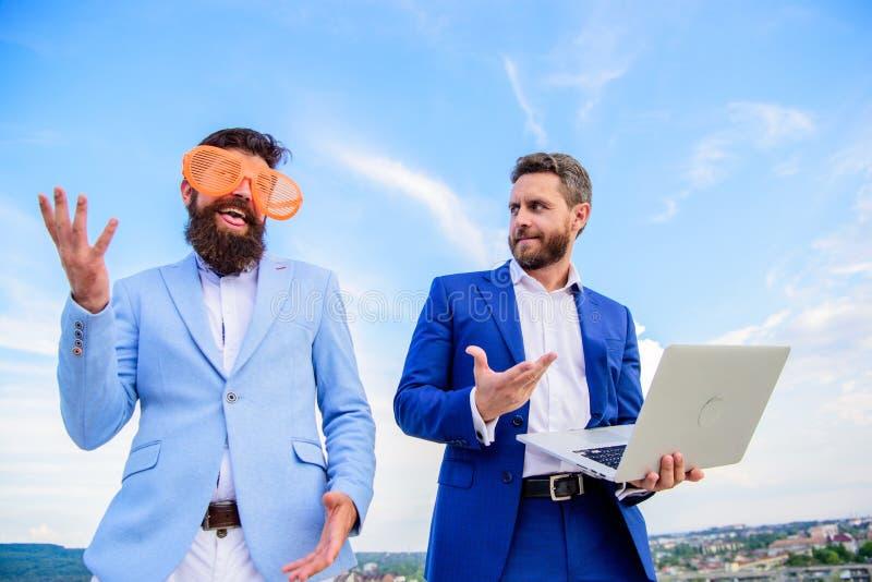 与严肃的膝上型计算机的商人,当商务伙伴可笑玻璃看起来滑稽时 如何停止使用在 免版税库存图片