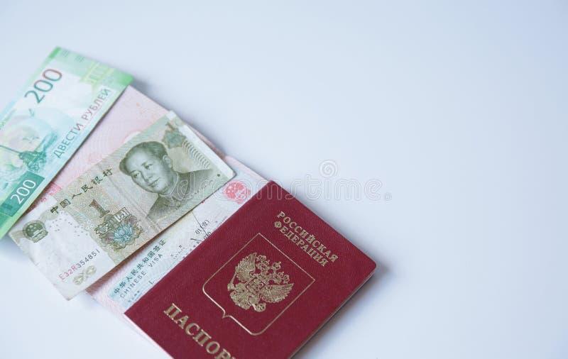 与中国签证和金钱的俄国护照是一元和200俄罗斯卢布 签证图章,护照 假期和旅行 免版税库存图片