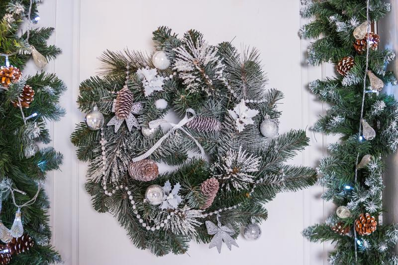 与中看不中用的物品、锥体和常青树大树枝的圣诞节花圈在一个白色门 在门的花圈装饰圣诞节的 图库摄影