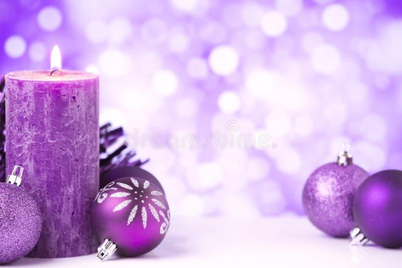 与中看不中用的物品和蜡烛的紫色圣诞节场面 图库摄影