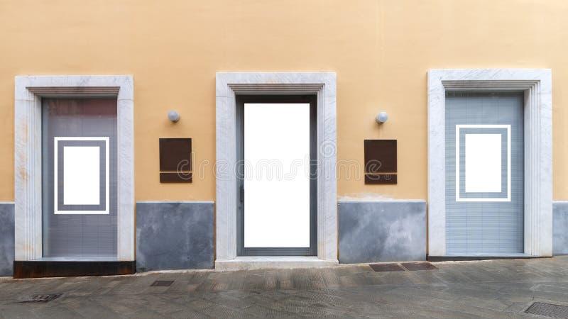 与中间两个空白的古铜色标志的三个空白的商店窗口大模型的 图库摄影