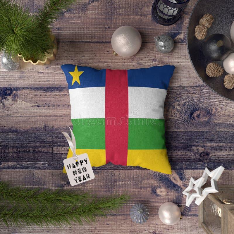 与中非旗子的新年快乐标记在枕头 在木桌上的圣诞装饰概念与可爱的对象 库存图片