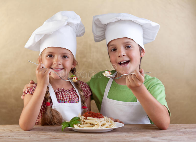 与主厨帽子的愉快的孩子吃新鲜的意大利面食的 图库摄影