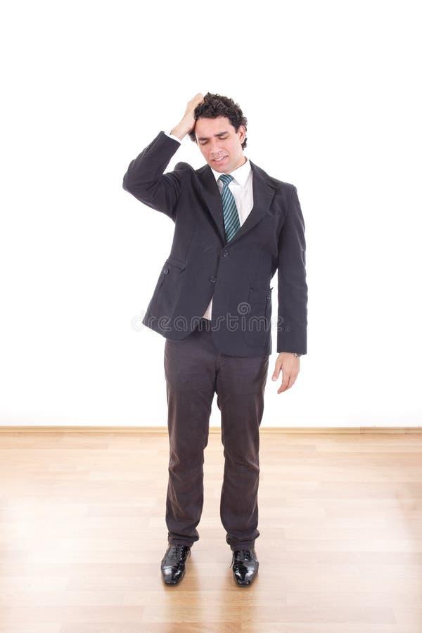 与举行他的h的头疼的沮丧和沮丧的商人 免版税图库摄影