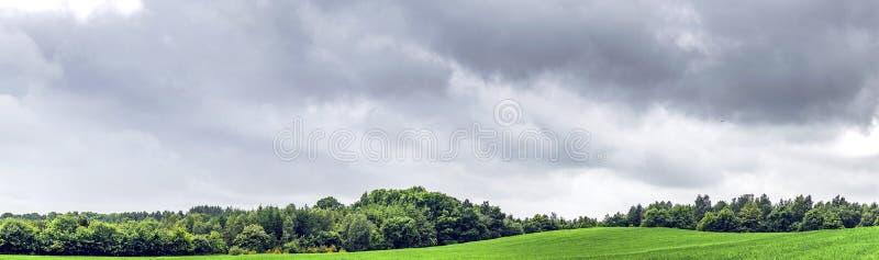 与乌云的农村全景风景 免版税库存图片