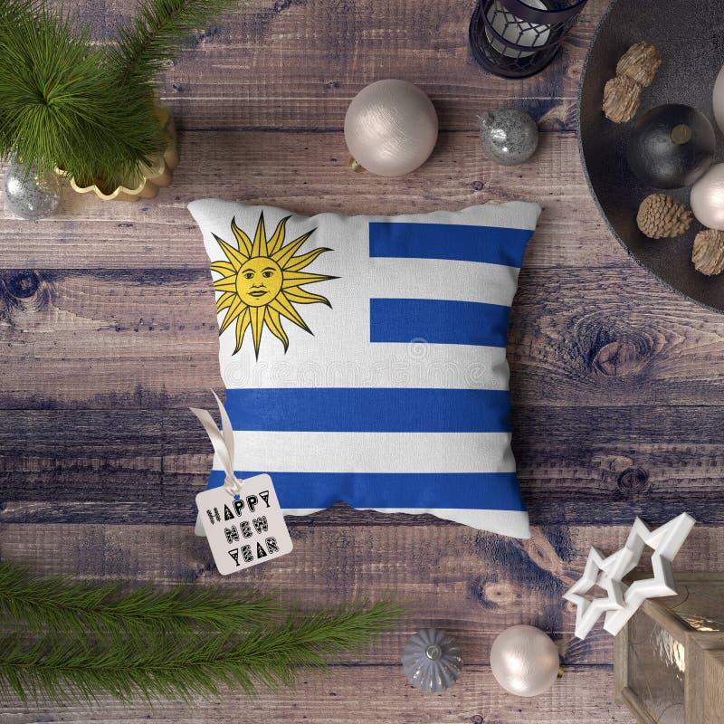 与乌拉圭旗子的新年快乐标记在枕头 在木桌上的圣诞装饰概念与可爱的对象 免版税库存照片