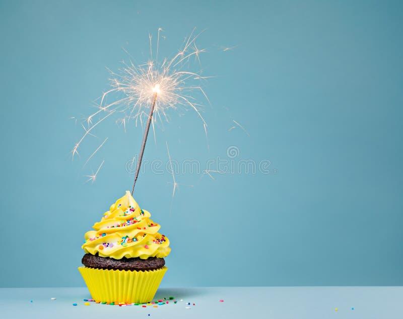 与乐趣闪烁发光物的黄色生日杯形蛋糕 库存图片
