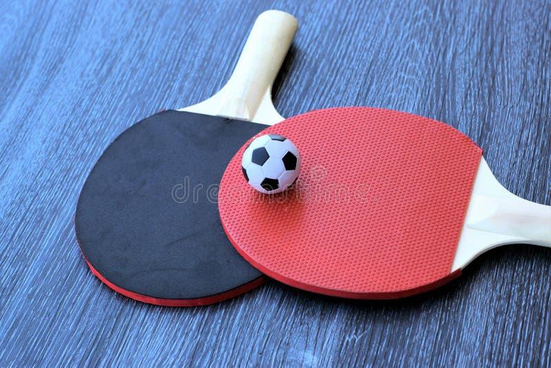 与乒乓球球拍的橄榄球 免版税库存图片