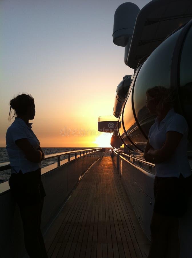 与乘员组的超级游艇日落 免版税库存照片