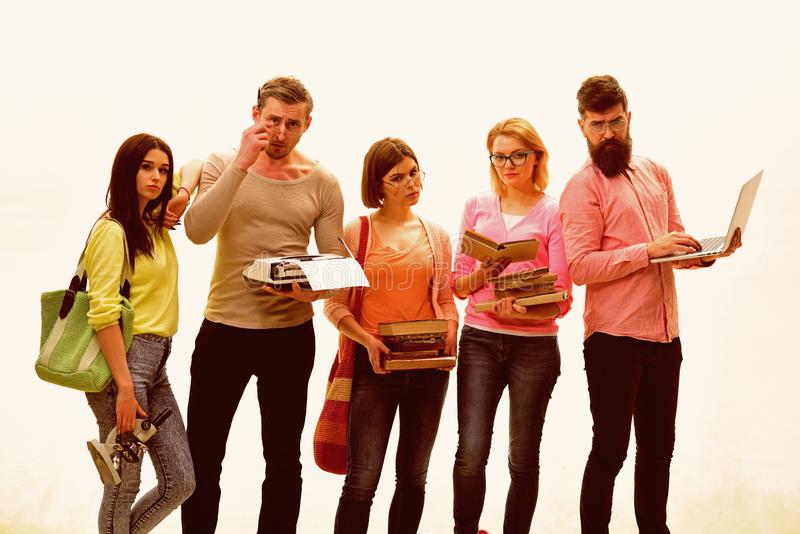 与书、袋子和膝上型计算机的青年时期 学生,朋友,小组与学生属性联接摆在,白色背景 库存图片