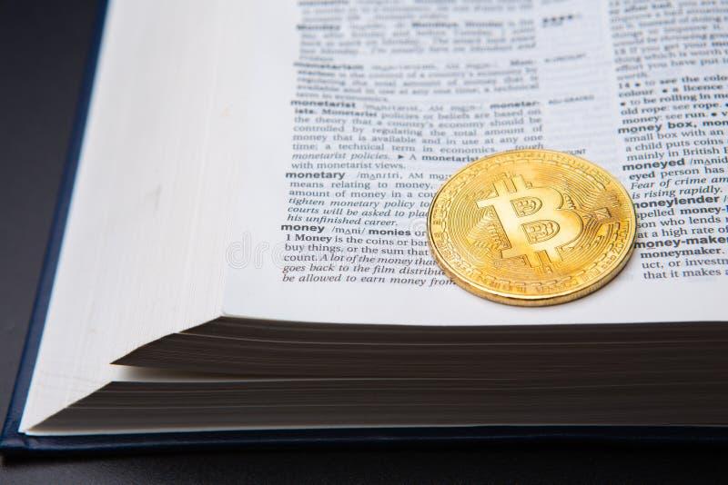 与书的一张在页的桌和bitcoin与金钱定义 免版税库存图片