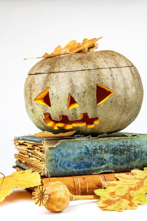 与书的万圣节南瓜在白色背景 万圣夜南瓜,滑稽的杰克O `灯笼 罪恶面孔鬼的假日 免版税库存图片