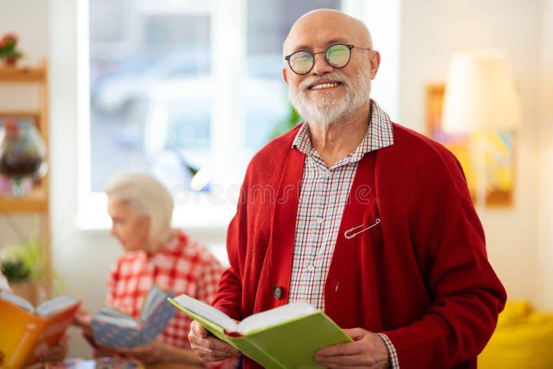 与书的快乐的愉快的年迈的人身分 库存照片