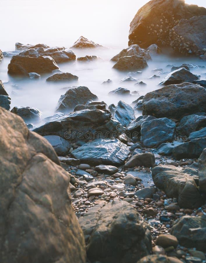 与乳状波浪的海滩岩石 库存照片
