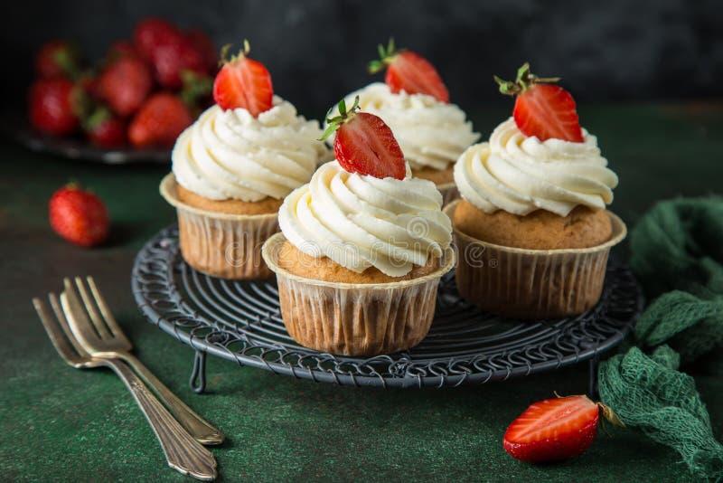 与乳脂干酪结霜和新鲜的草莓的香草杯形蛋糕 库存图片
