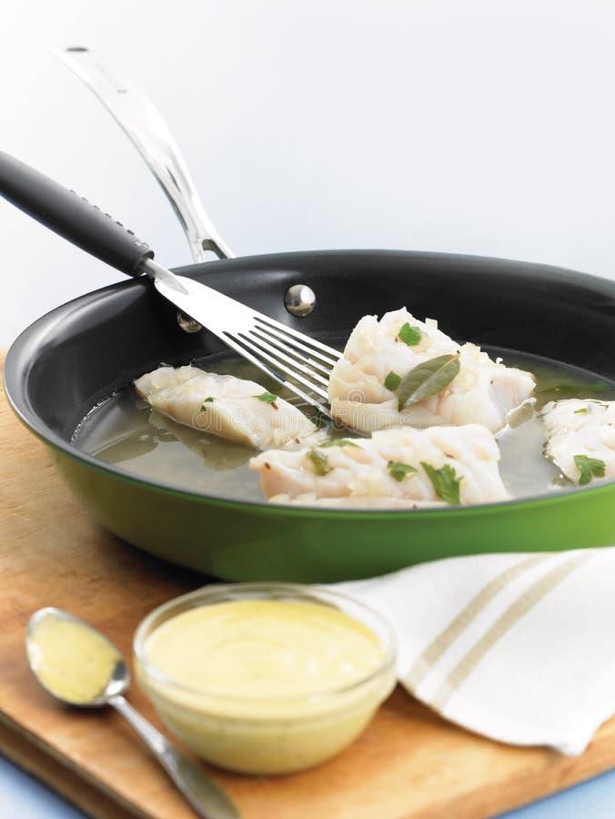 与乳脂状的蒜泥蛋黄酱的水煮的白色鱼 免版税库存照片