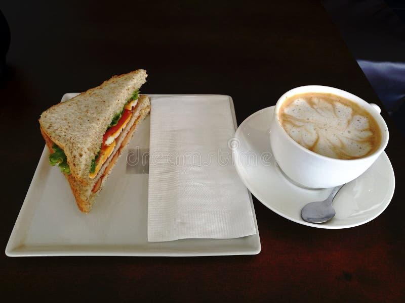 与乳酪和火腿和拿铁咖啡杯的自创三明治在白色板材的n a在绿色木桌上 库存图片