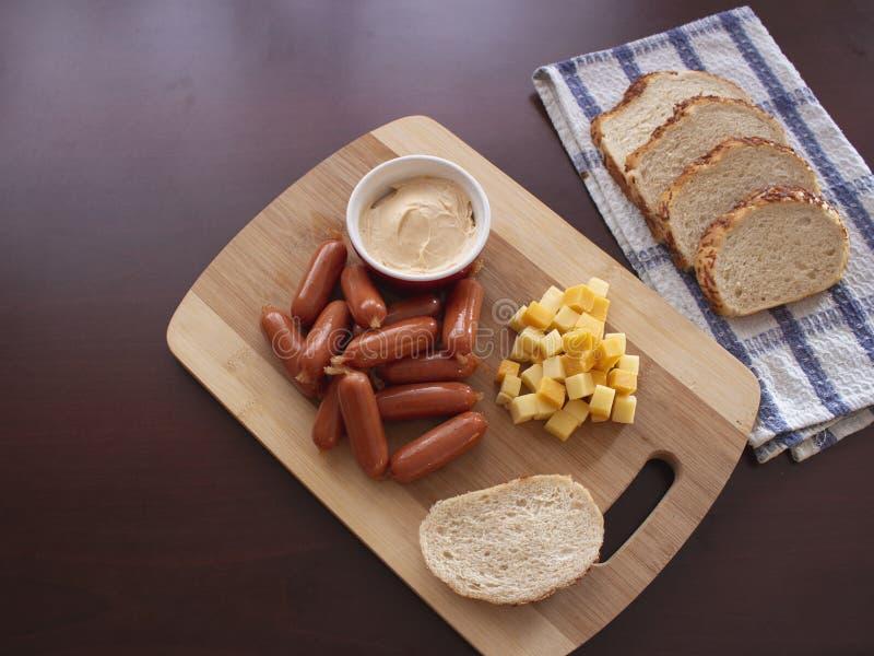 与乳酪立方体和土豆面包切片的辣垂度混合的微型熏制的香肠鸡尾酒熏肉香肠 免版税库存图片